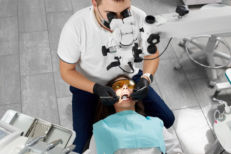 Male dentist with an assistant in a black mask and gloves treats a patient using a microscope. Modern dentistry with the use of new technologies Stockfoto