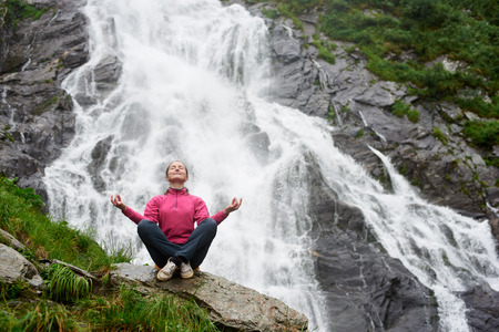 Cheerful female tourist smiling sitting in lotus position near waterfall meditating with her eyes closed copyspace harmony calamity balance asana happiness nature travelling emotions tourism. Stock Photo
