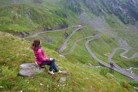 Girl sits on a stone enjoying wonderful mountain scenery. Transfagarashan Highway, the most beautiful road in Europe, Ridge Fagaras
