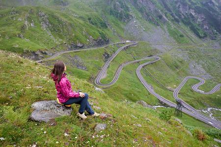 Girl sits on a stone enjoying wonderful mountain scenery. Transfagarashan Highway, the most beautiful road in Europe, Ridge Fagaras
