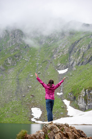 Woman is standing with her back on a rock with her arms wide open and looks up against background of mighty mountains and the lake at the foot, Transylvania, Romania.