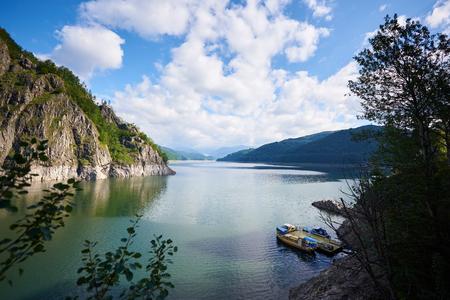 Lake Vidraru, romanian Lacul Vidraru, is an artificial lake in Romania in Fagaras mountains. Blue sky with clouds above it