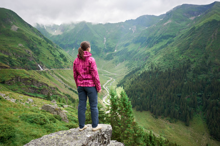 Female tourist enjoys the beautiful scenery of the valley of green mountains, clouds hanging over them and Transfagarashan Highway. The most beautiful road in Europe, Romania