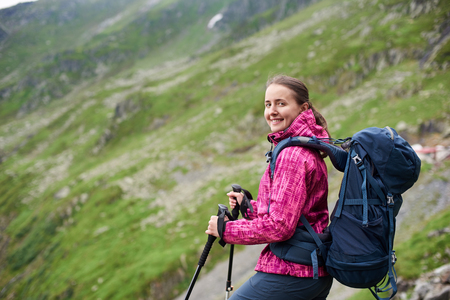Smiling female tourist with backpack and walking sticks posing in front of beautiful green rocky mountain near Transfagarshan winding road in Romania. Woman climber happy spectacular view grassy slope