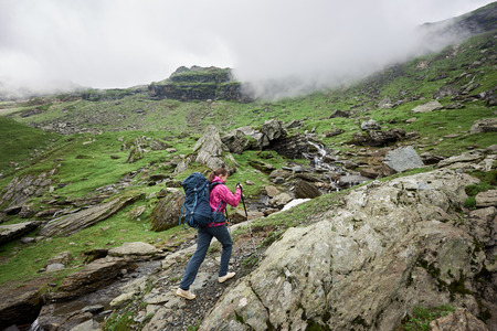 Girl hiker climbs to the top of the mountainous country of Romania. Clouds shroud mountains. Woman with backpack and trekking sticks