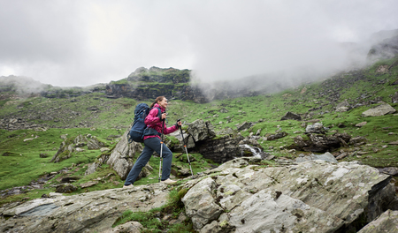 Woman backpacker with trekking sticks and backpack climbs of Romania mountains. Clouds shroud mountains