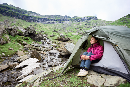 Happy tourist female sits in a tent near a mountain stream in a rocky terrain of Fagaras Mountains. Stock Photo