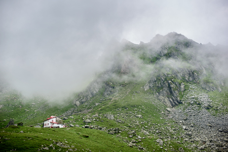 Fog descends to the mountains in the valley of the Fagaras Mountains. Lonely house in the valley at Transylvania, Romania, Europe. Stock Photo