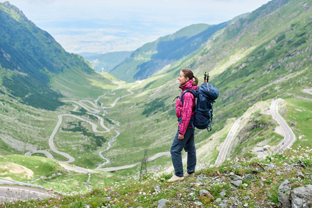 Full length shot of a woman standing on top of a hill enjoying the scenery of Transfagarasan road in Romania while travelling copyspace tourism exploring lifestyle Europe.