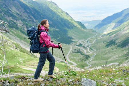 Cheerful woman hiker with a backpack smiling looking away enjoying beautiful mountains landscape copyspace Transfagarasan road on the background travelling hiking tourism active living.