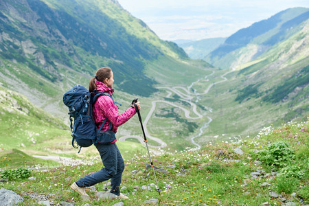 Hiking trip in the mountains of Romania. Girl with a backpack and trekking sticks on a blurred background of a picturesque landscape most beautiful road in Europe - Transfagarashan Highway