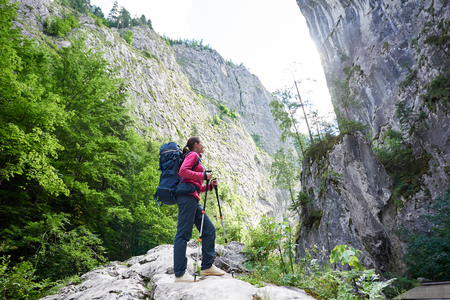 Hiker girl in modern outfit with blue backpack and trekking sticks standing before enormous stone cliff wall. Young hiker woman in pink jacket and gray pants enjoying view of high a mountain. Stock Photo