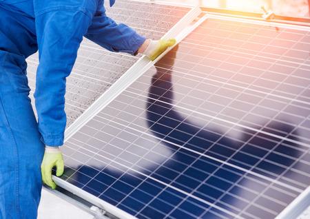 Proceso de instalación de baterías solares en invierno. Trabajador en uniforme azul y guantes. De cerca Foto de archivo