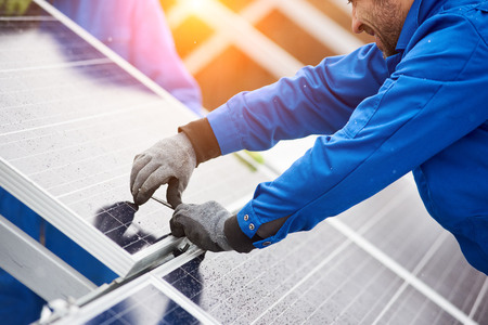 Smiling male technician in blue suit installing photovoltaic blue solar modules with screw. Man electrician panel sun sustainable resources renewable energy source alternative innovation Stok Fotoğraf