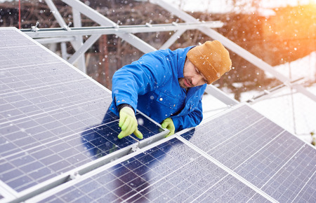 Guy with the help of tools installs solar panels in snowy weather. He is dressed in uniform and gloves