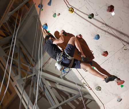 Muscular man practicing rock-climbing on a rock wall indoors. The concept of sport and health at any time of year Stock Photo