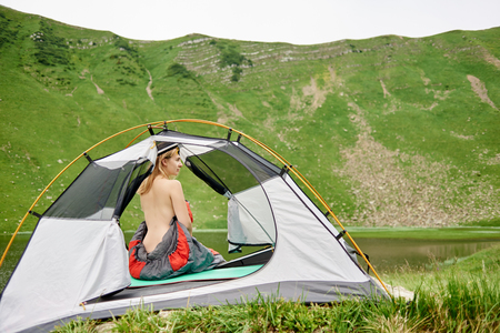 Back view of sporty naked female hiker sitting in tent in sleeping bag, enjoying beautiful view of lake in the mountains. Camping lifestyle concept adventure summer vacations outdoor