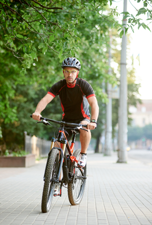 Young bicyclist in cycling sportswear riding on bike near green park. Cyclist shooting for clothing advertisement campaign. Concept of healthy lifestyle, sport advertising, outdoor activities Imagens