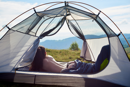 Back view of attractive naked female traveller lying in tent in sleeping bag, enjoying summer day in the mountains. Camping lifestyle concept Standard-Bild