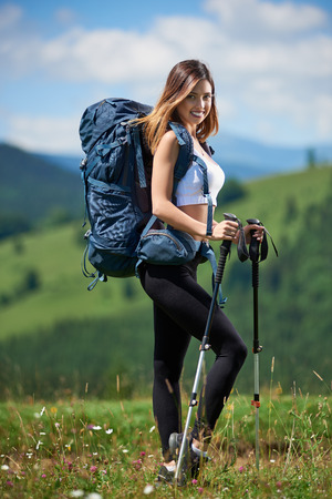 Full-length portrait of beautiful sporty girl hiker with blue backpack and trekking poles posing on the top of a hill, smiling to the camera in the mountains. Concept of active lifestyle