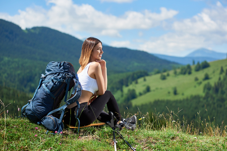 Pretty sporty girl traveller with backpack resting on the top of a hill, looking away, enjoying summer day. Mountains, forests and cloudy sky on the blurred background. Copy space