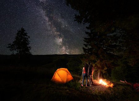 Rear view of young couple tourists enjoying the starry sky with a bright Milky way under the mighty trees near the campfire and orange illuminated tent in mountains. Romantic night camping near forest Stock fotó