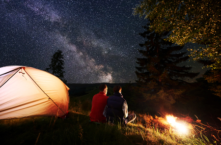 Rear view romantic couple tourists having a rest in the camping at night, sitting by the campfire and glowing orange tent near forest against a background of night sky with stars and Milky way. Stock fotó