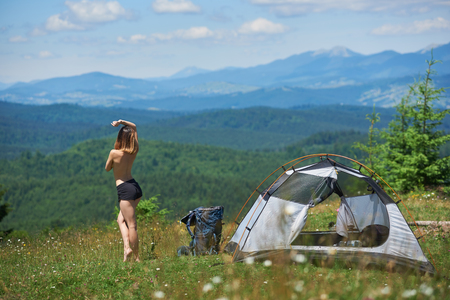 Back view of attractive naked female hiker posing near the tent and backpack, enjoying summer day in the mountains. Camping lifestyle concept adventure vacations outdoor 版權商用圖片