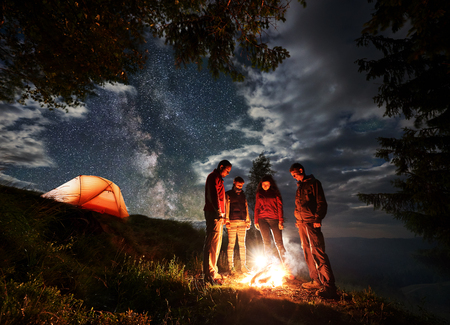 Group of young tourists standing around the campfire near trees and illuminated orange tent under cloudy sky with stars and Milky way. Night camping in the mountains