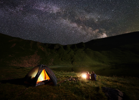 Night camping in the mountains near lake under the sky strewn with stars and bright Milky way. Rear view of boy and girl hikers having a rest near campfire and illuminated tent, enjoying the scenery Stock fotó