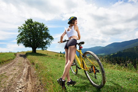 Wide angle view of attractive female cyclist riding on yellow bicycle on a rural trail in the mountains, wearing helmet. Big tree and cloudy sky on the background. Outdoor sport activity
