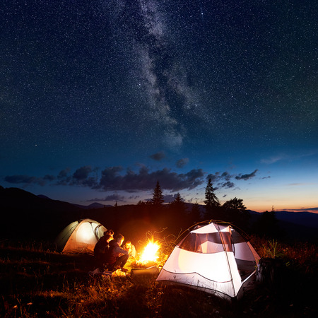 Family hikers mother, father, two sons having a rest at night camping in mountains, sitting on log beside campfire and two illuminated tents, under amazing view of evening sky full of stars, Milky way