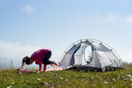 Young slim barefooted girl doing gymnastic exercises on green grass at small tourist tent under beautiful blue sky on bright sunny morning. Sport, tourism and mountain camping concept.