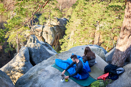 Morning view from above of young tourist couple in mountains, handsome bearded man and pretty long-haired girl sitting in sleeping bags and having coffee on big rocks between trees. Tourism concept.