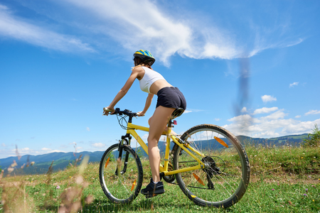 Wide angle view of active woman rider cycling on yellow mountain bike on a rural trail, against blue sky with clouds. Outdoor sport activity, lifestyle concept. Copy space Stock Photo