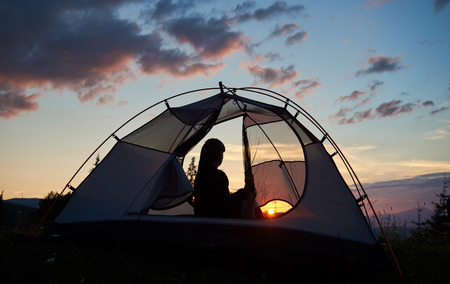Rear view girl hiker sitting in a tent under the morning blue sky enjoying the dawn on the background of the bright rising sun over the mighty mountains. View through a tent 免版税图像