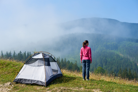 Back view of young tourist woman standing on blooming valley at tourist tent under beautiful clear blue sky, enjoying foggy mountains view on summer morning. Tourism and traveling concept.