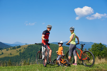 Young happy family tourists bikers, mom, dad and child resting with bicycles on grassy hill, looking in camera. Mountains view and blue sky on background. Healthy lifestyle and relations concept. Stockfoto