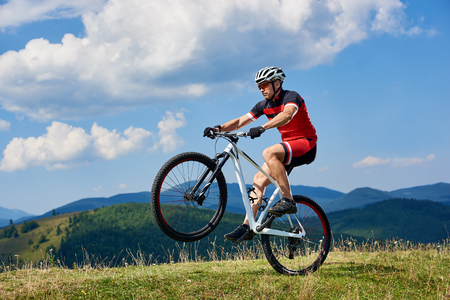 Athletic sportsman cyclist in professional sportswear and helmet riding cross country bike, turning on one wheel of bicycle on mountain hill. Blue summer sky on background. Extreme sport concept