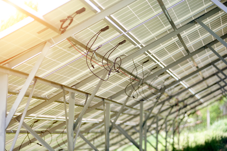 Interior of stand-alone photo voltaic solar system secured on metal rear legs lit by summer sun. Alternative energy, ecology and environment protection and cheap electricity production concept. Imagens