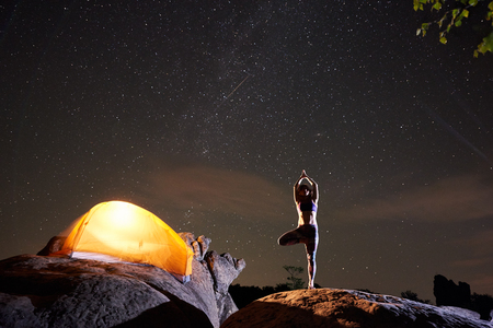 Brightly lit tourist tent and young slim woman standing on one leg with raised arms doing yoga at night on huge boulder under dark starry sky. Tourism, nature and active lifestyle concept. Vrikshasana