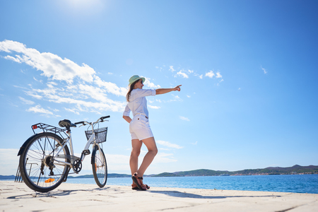 Attractive woman in white closing and sunhat standing at bicycle on stony sidewalk under clear blue sky pointing at opposite shore on sparkling clear water background. Tourism and vacations concept.