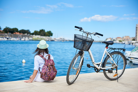 Back view of young woman in white closing, sunhat and with backpack sitting at bicycle on stony sidewalk under clear blue sky on sparkling clear bay water background. Tourism and vacations concept. Stock Photo