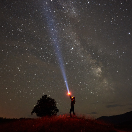 Silhouette of woman standing against night starry sky with Milky Way in the mountains with a flashlight in his hand