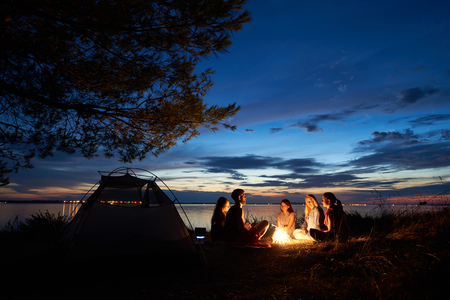 Night summer camping on lake shore. Group of five young tourists sitting on the beach around campfire near tent under beautiful blue evening sky. Tourism, friendship and beauty of nature concept. Stock Photo