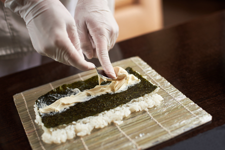 Close-up view of process of preparing rolling sushi. Nori, white rice and chees on bamboo mat. Chefs hands in gloves starts cooking sushi rolls Imagens