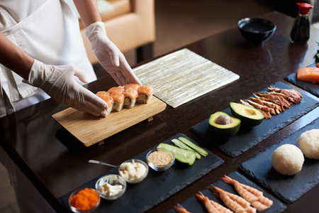 Close-up view of process of preparing rolling sushi. Chef is serving fresh delicious rolls on the wooden board.