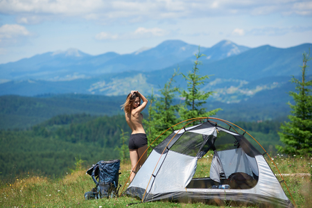 Back view of sporty naked woman tourist standing near the tent and backpack