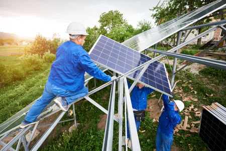 Installing of stand-alone solar voltaic panel system. Team of three technicians in hard-hats mounting the solar module on platform on green summer view background. Alternative energy concept. Stock Photo