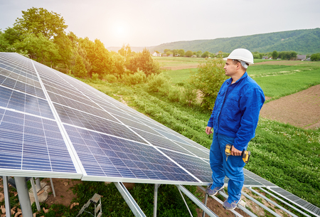 Construction worker with screwdriver standing on metal frame of voltaic solar system looking on shiny surface. Alternative energy, ecology protection and cheap electricity production concept.